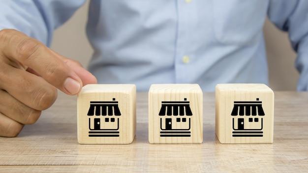 La mano del primo piano sceglie i blocchi di legno del giocattolo del cubo impilati con l'icona del negozio di affari di franchising.