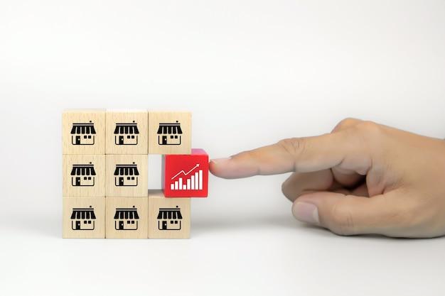 La mano del primo piano sceglie l'icona del grafico sui blocchi di legno del giocattolo del cubo impilati con l'icona del negozio di affari di franchising.