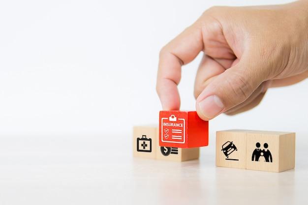La mano del primo piano sceglie i blocchi di legno rossi impilati con l'icona di assicurazione.