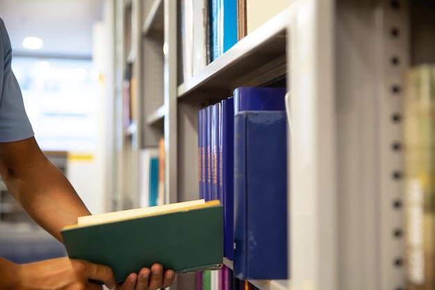 Chiudere la mano scegliendo un libro dallo scaffale.