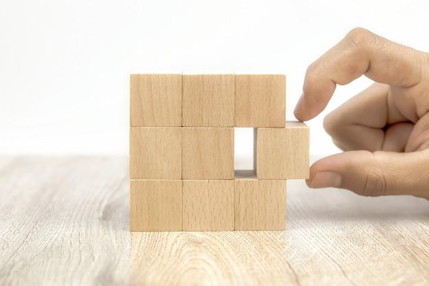 Mano del primo piano che sceglie il giocattolo del blocco di legno del cubo impilato senza grafica.