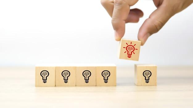 Chiuda sulla mano che sceglie un'icona della lampadina sui blocchi di legno del giocattolo del cubo.