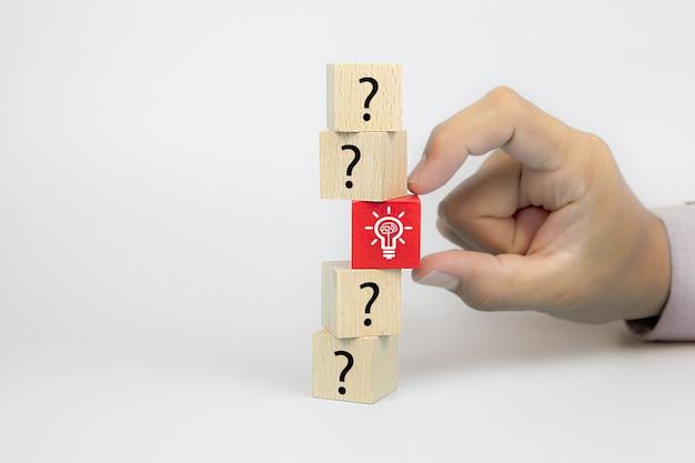 Chiuda sulla mano scegliendo un'icona della lampadina dal simbolo del punto interrogativo sui blocchi di legno del giocattolo del cubo