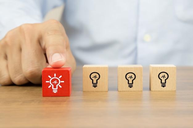 Chiuda sulla mano scegliendo le icone della lampadina sui blocchi di legno del giocattolo del cubo