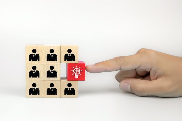 Chiuda sulla mano che sceglie una lampadina sull'icona della gente sui blocchi di legno del giocattolo del cubo