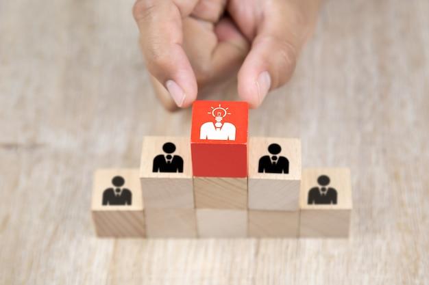Chiuda sulla mano scegliendo le icone della gente con una lampadina sui blocchi di legno del giocattolo del cubo impilati.