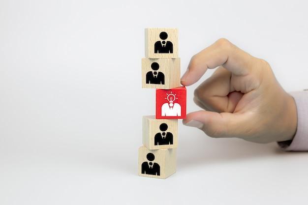 Chiuda sulla mano scegliendo le icone delle persone con una lampadina sui blocchi di legno del giocattolo del cubo.