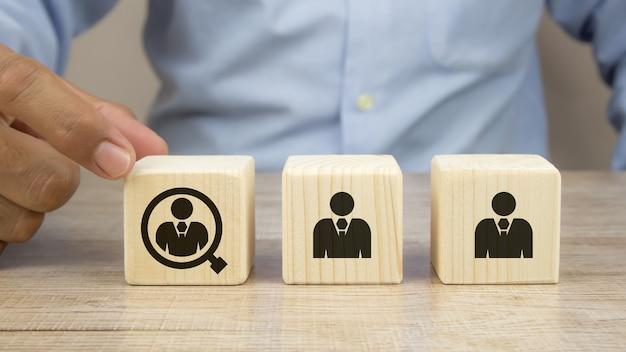 Chiuda sulla mano che sceglie le persone in un'icona di lente di ingrandimento sui blocchi di legno del giocattolo del cubo