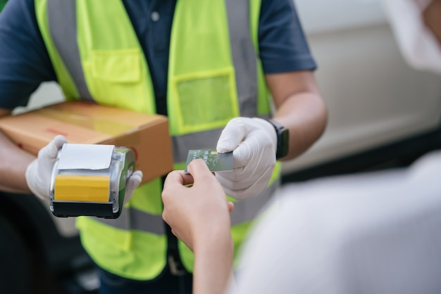 Il fattorino ravvicinato accetta la carta di credito utilizzando un lettore di carte di credito durante la consegna di prodotti ai clienti a casa, concetto di contrassegno con carta di credito.