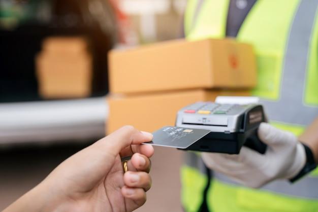 Chiuda in su del fattorino della mano che utilizza la macchina di scorrimento della carta di credito per pagare. mano con la carta di credito che scorre attraverso il terminale per il pagamento all'esterno del magazzino, selezionare la carta di credito focus.