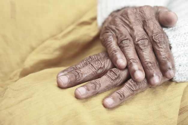 Stretta di mano di una persona anziana su giallo