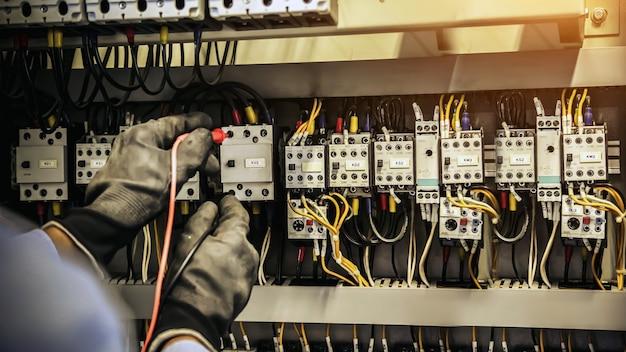 Chiuda sulla mano dell'ingegnere elettrico che controlla la tensione della corrente elettrica all'interruttore