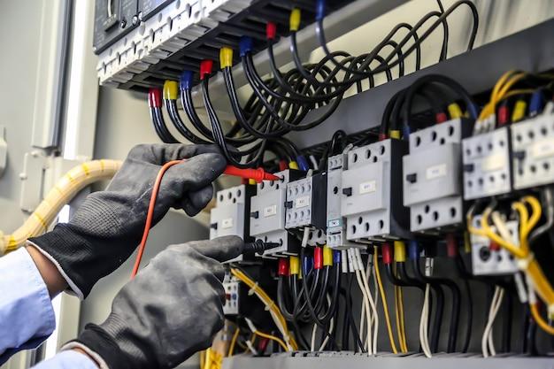 Primo piano mano di ingegneria elettrica utilizzando la misurazione per controllare l'elettricità.