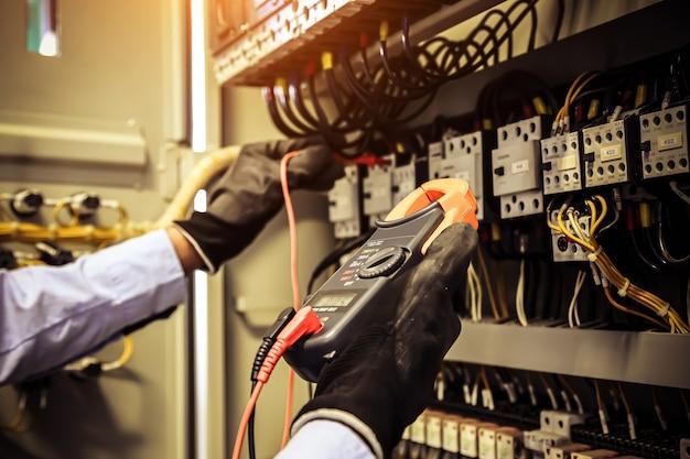 Mano ravvicinata di ingegneria elettrica utilizzando la misurazione per controllare l'elettricità.