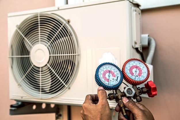 Chiudere la mano dell'ingegnere utilizzando il manometro per il riempimento dei condizionatori d'aria.