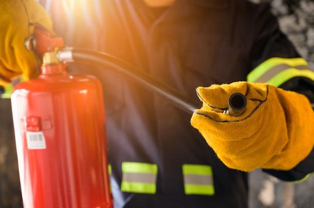 Chiuda sul vigile del fuoco della mano facendo uso del combattimento dell'estintore.