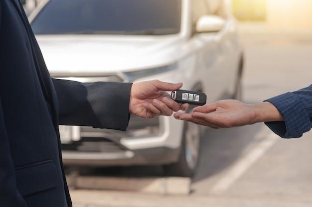 Chiuda sulla mano che dà automobile di vendita di concetto di automobile chiave, compri l'affitto, finanza, servizio