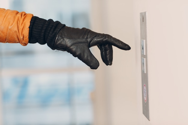 Primo piano dell'indice della mano nel guanto che preme l'ascensore del pulsante durante il concetto di quarantena covid-19 della pandemia di coronavirus