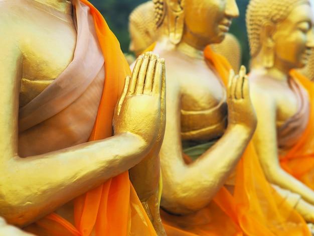 Chiuda sulla mano delle statue dorate del monaco che si siedono in una fila alla provincia di nakornnayok del tempio pubblico, tailandia