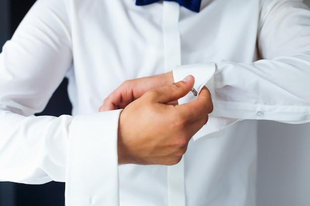 Primo piano di una mano sposo come indossa la camicia bianca e il gemello