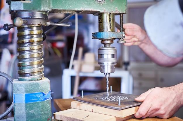 Avvicinamento. il lavoratore industriale pesante della mano sta lavorando al processo della fabbrica della lavorazione dei metalli