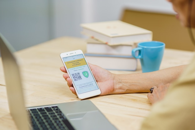Primo piano tenere in mano lo schermo del telefono cellulare del passaporto vaccinale del certificato di immunità covid19 a casa