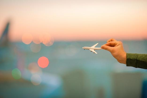 Chiuda sulla mano che tiene un modello dell'aeroplano
