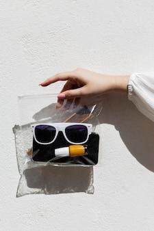 Chiuda sulla borsa della holding della mano con gli oggetti