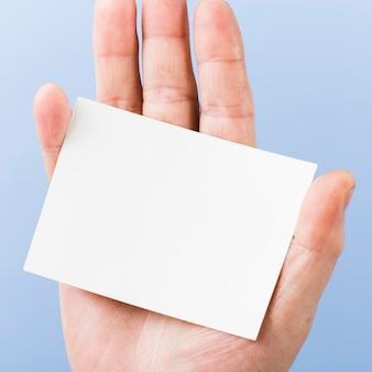 Mano del primo piano che tiene il biglietto da visita della carta in bianco