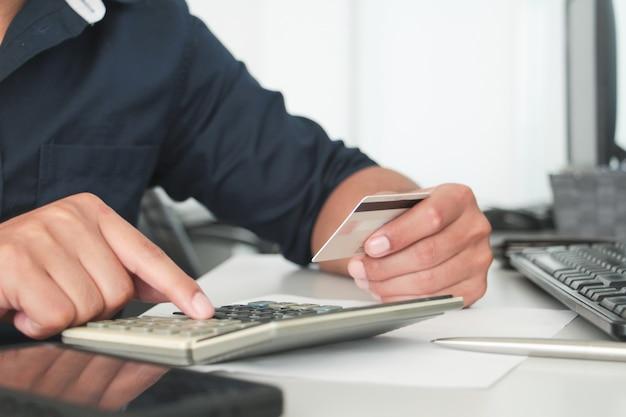 Chiuda sulla mano che tiene la carta di credito o bancomat e dito sfocato touch callulator in ufficio. concetto di ufficio di lavoro. concetto di pagamento digitale. conto o finanziario. acquisto o concetto di acquirente.