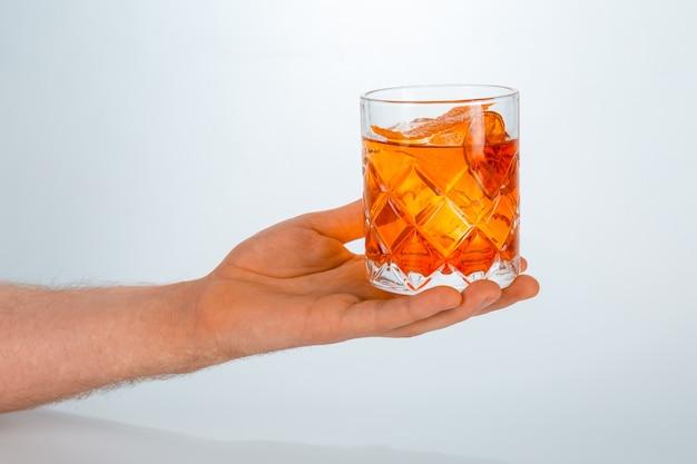 Chiuda in su di una mano che tiene un vetro del cocktail di negroni su bianco con lo spazio della copia.