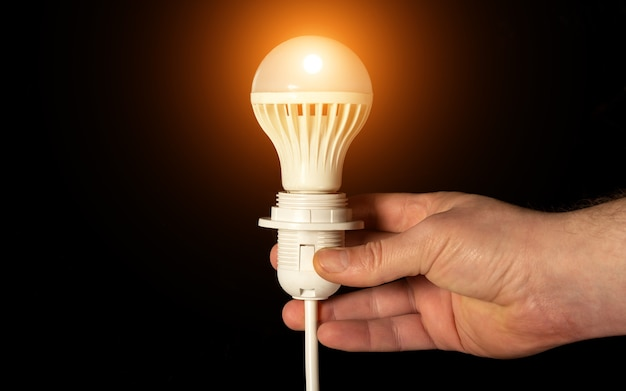 Primo piano di una mano che tiene una lampadina incandescente