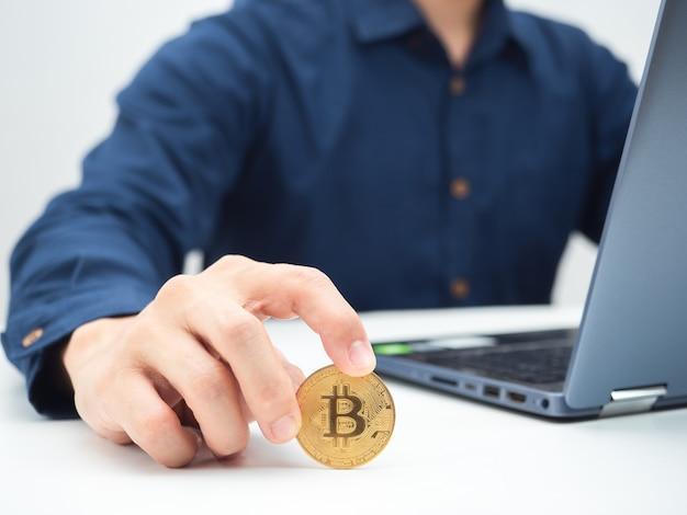 Mano ravvicinata che tiene bitcoin dorato sul tavolo con un colpo di ritaglio del laptop