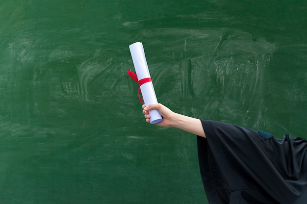 Primo piano mano che tiene il certificato di laurea
