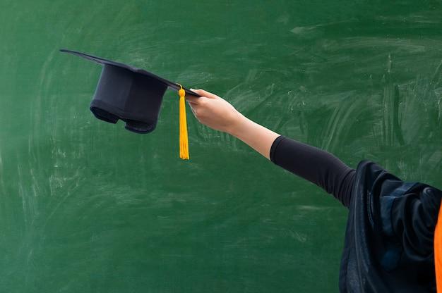 Stretta di mano che tiene il cappello di laurea