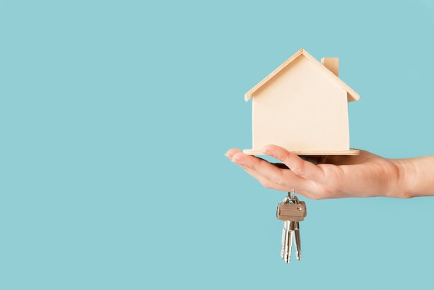 Primo piano delle chiavi della tenuta della mano e del modello di legno della casa contro fondo blu