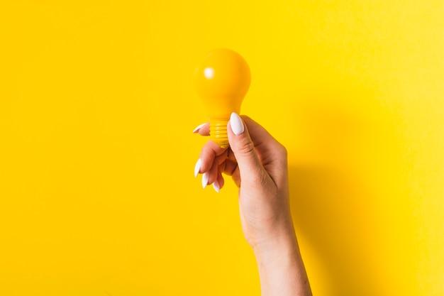 Primo piano della mano che tiene la lampadina su sfondo giallo