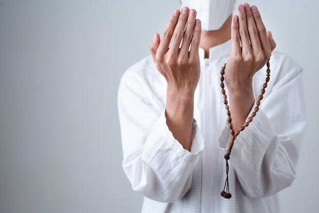 Primo piano mano che tiene un musulmano perline o tasbih con su grigio