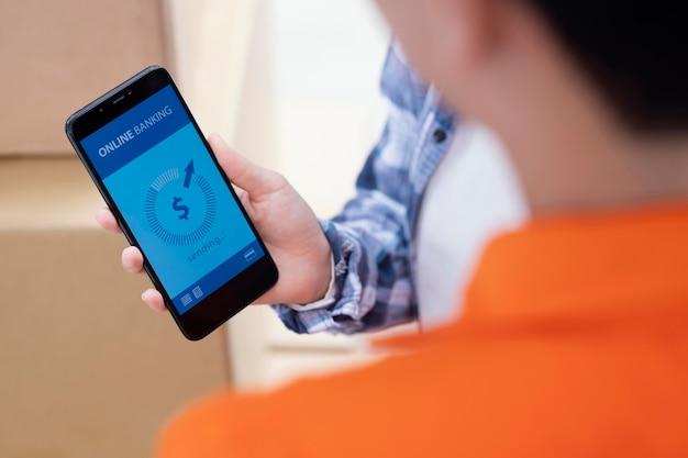 Primo piano a portata di mano che tiene il telefono con app bancaria