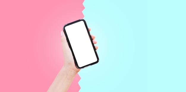 Primo piano della mano che tiene smartphone su due colori: rosa e ciano