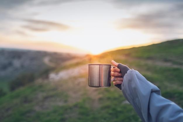 Primo piano della mano che tiene la tazza in acciaio con una bevanda calda sul tramonto.