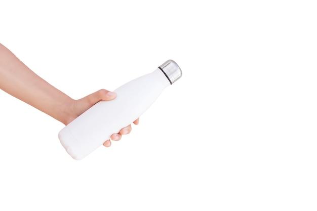 Primo piano della mano che tiene la bottiglia d'acqua termo riutilizzabile d'acciaio isolata su bianco con lo spazio della copia.