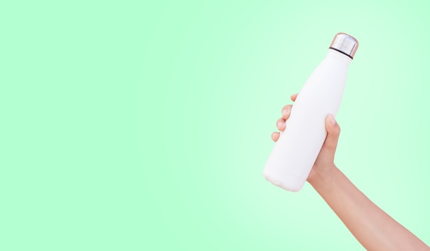 Primo piano della mano che tiene la bottiglia di acqua termica d'acciaio riutilizzabile bianca isolata sul verde con lo spazio della copia.