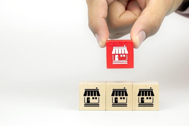 La mano del primo piano sta scegliendo i blocchi di legno del giocattolo del cubo impilati con l'icona del negozio di affari di franchising
