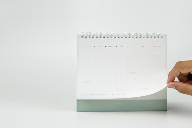 La mano del primo piano è aprire il calendario in bianco su una superficie bianca
