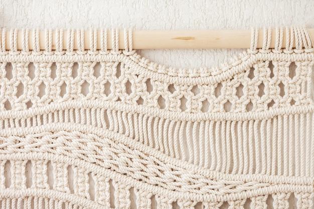 Struttura del macrame fatta a mano del primo piano. maglieria moderna ecologica. concetto di decorazione naturale all'interno. lay piatto. macramè fatto a mano 100% cotone.