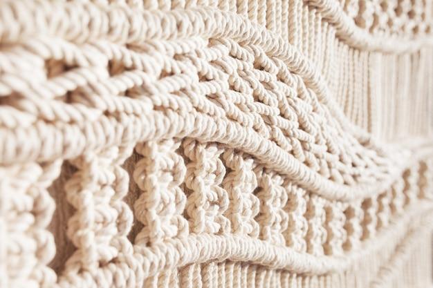 Primo piano del reticolo di struttura del macramè fatto a mano. concetto di decorazione naturale fai-da-te fai-da-te moderno ecologico all'interno. macrame fatto a mano 100% cotone. passatempo femminile.