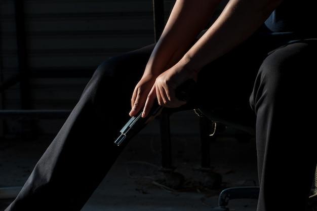 Primo piano della mano di un uomo che porta una pistola con un proiettile nella camera