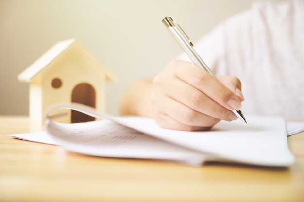 Chiuda sulla mano dell'uomo che firma il documento di prestito della firma alla proprietà domestica.