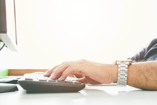Chiudere la mano dell'uomo con la tastiera e il vecchio display srceen. concetto di ufficio di lavoro. lavoro di concetto impegnativo e serio. concetto di salaryman.